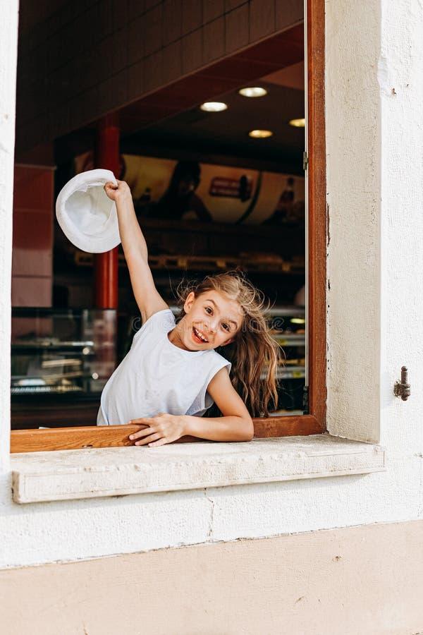 Girl hat waves through window joy emotions. Girl with a hat waves through the window joy and emotions, cheerful, happy, positive, child, caucasian, joyful stock image