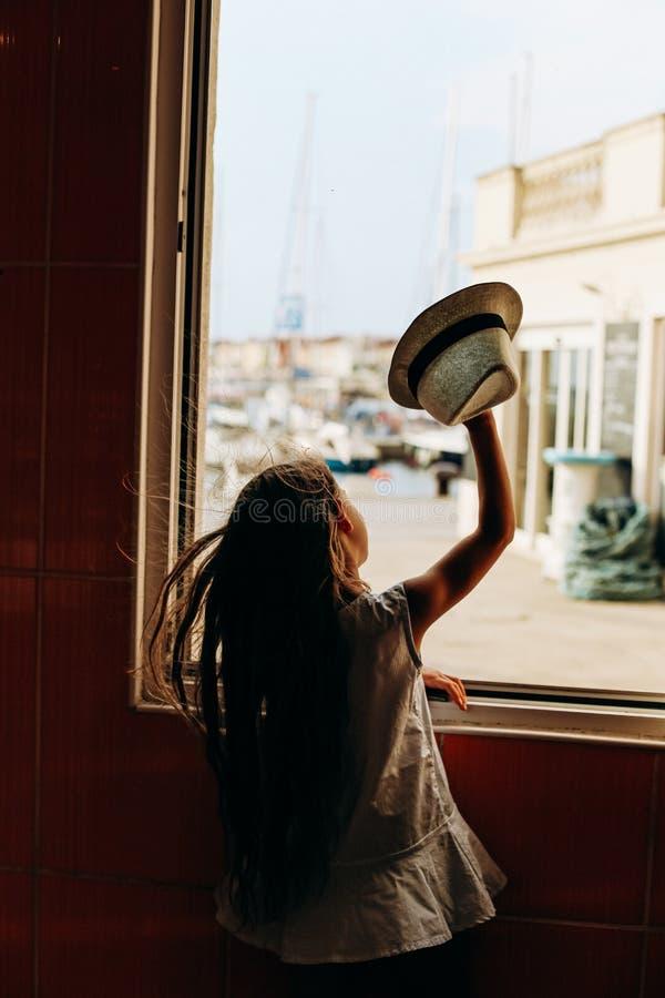 Girl hat waves through window joy emotions. Girl with a hat waves through the window joy and emotions, cheerful, happy, positive, child, caucasian, joyful royalty free stock photo
