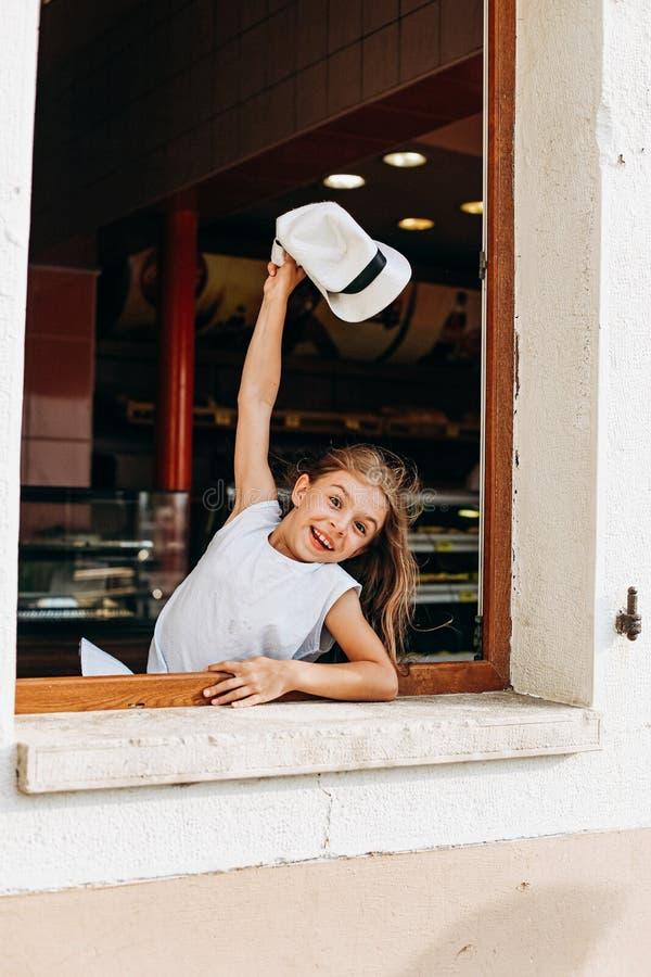 Girl hat waves through window joy emotions. Girl with a hat waves through the window joy and emotions, cheerful, happy, positive, child, caucasian, joyful stock photography