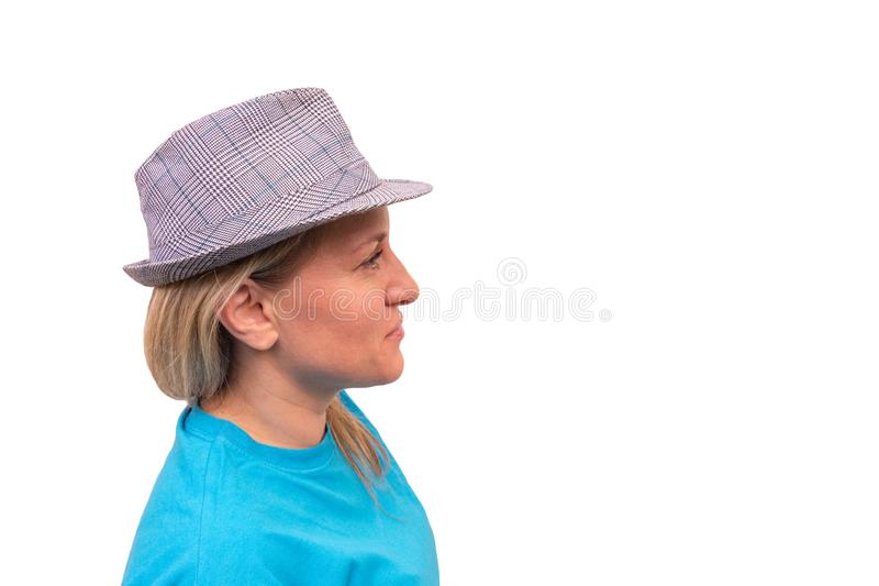 Girl in hat. White middle aged woman looks away and smiles. Profile portrait with positive face royalty free stock photography
