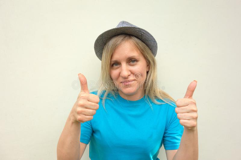 Girl in hat. White middle aged woman looks at camera and shows thumbs-up gesture by two hands. Front portrait with positive face royalty free stock photo