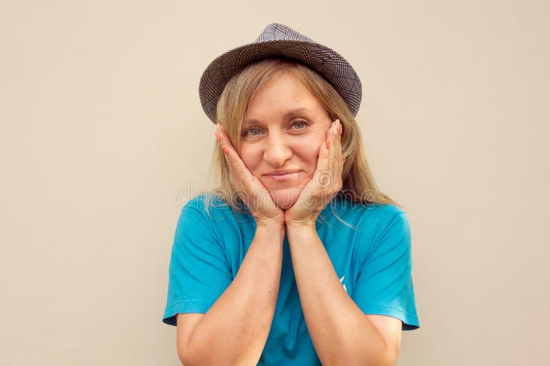 Girl in hat. White middle aged woman looks at camera and touches her cheeks with hands. Front portrait with positive face stock photography