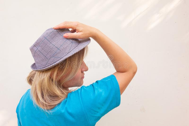 Girl in hat. White middle aged woman poses under sun beams. Profile portrait with calm face stock photos