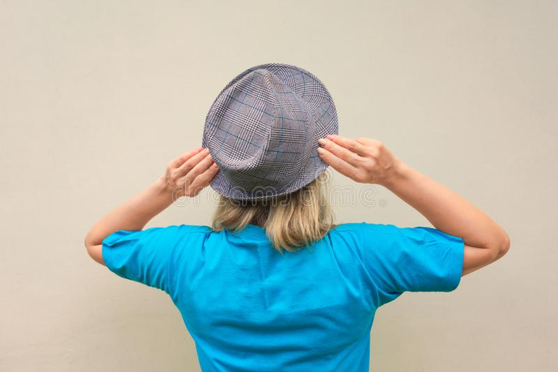 Girl in hat. White middle aged woman stays back to us and touches her hat's flaps. Back view with no face royalty free stock photo
