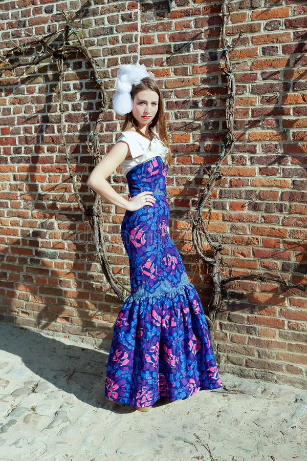 Girl haute couture dress. Girl in blue haute couture dress in front of a red brick stone wall with ivy standing in sandy ground royalty free stock photography