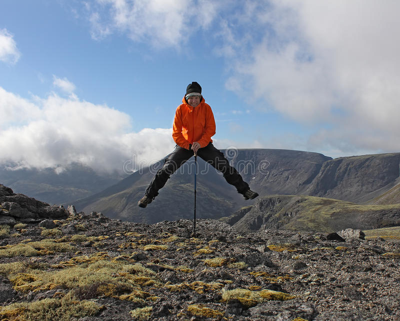 Girl have fun on top of the mountain - hanging on a trekking stick. Russia, Hibiny, tundra stock photo