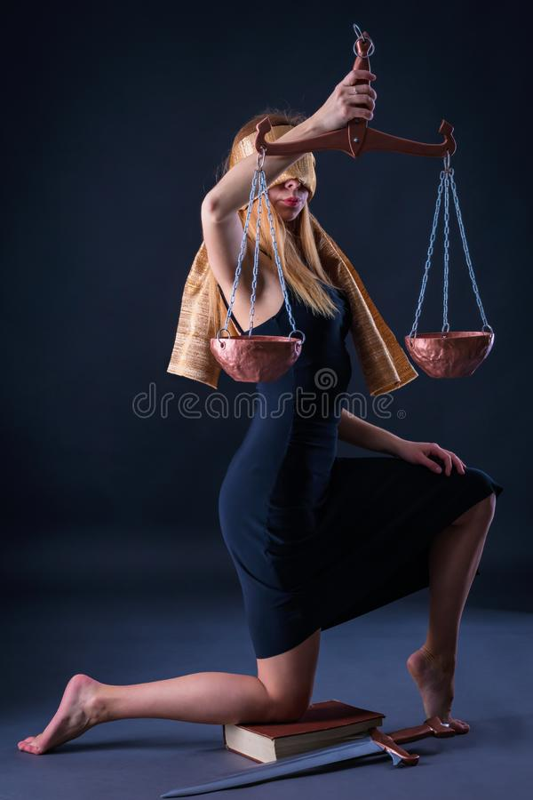 Girl, having bent a knee on the book with a sword, holds Libra in hand as Themis. The charming girl, having bent a knee on the book with a sword, holds Libra in stock image