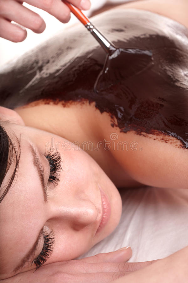 Girl having chocolate bodyl mask . stock photos