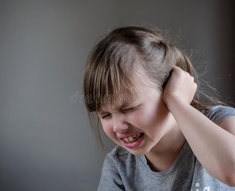Girl having ear pain touching his painful head isolated on gray background.  stock photos