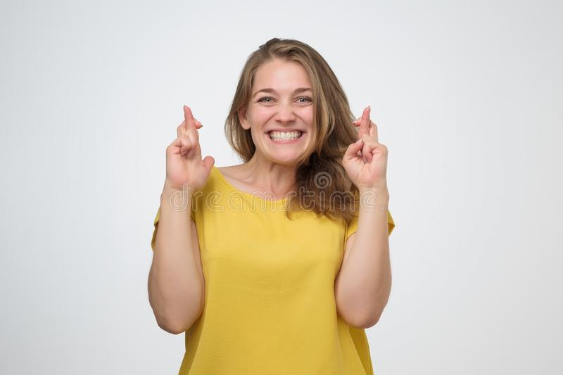 Girl having excited, superstitious and naive look, keeping fingers crossed stock image