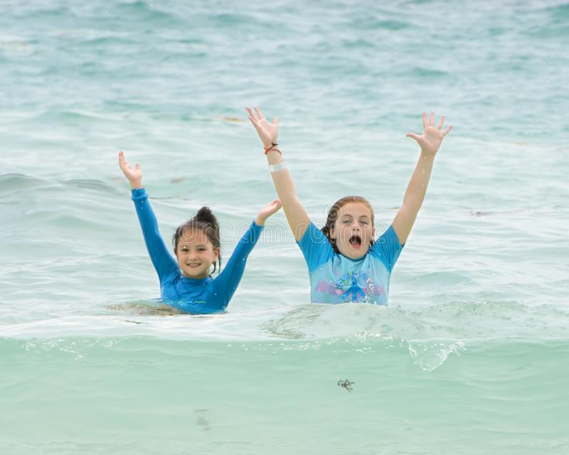 Girl3 having fun in the Caribbean Sea, Playa Paraiso, Tulum, Mexico. Pictured is an eleven year-old girl and her nine-year-old cousin standing chest deep in the stock images