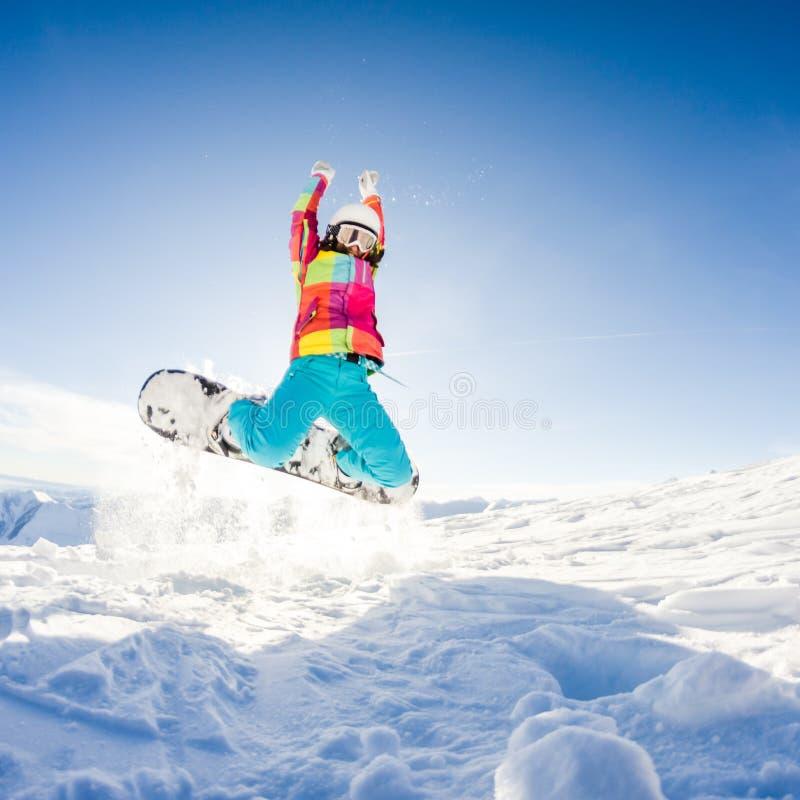 Girl having fun on her snowboard stock image