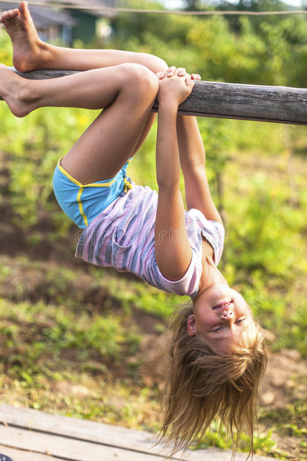 Girl having fun in park hanging upside down on green rural countryside. royalty free stock images