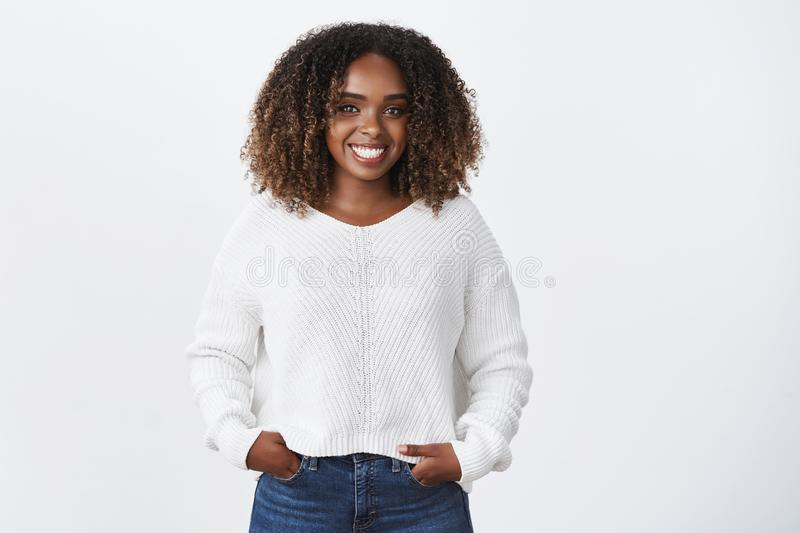Girl having fun talking to interesting person. Portrait of joyful charismatic smiling african-american young woman with. Curly hair in sweater holding hands in stock photos