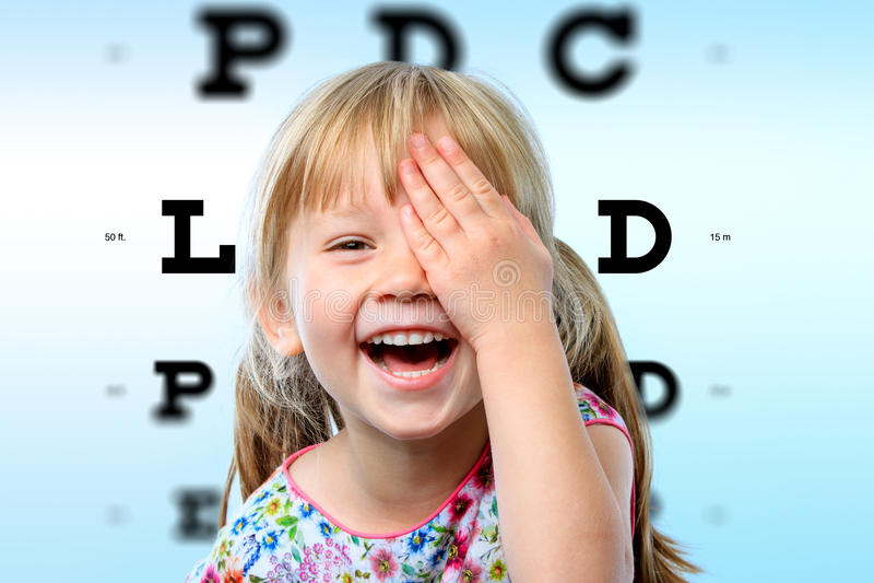Girl having fun at vision test. royalty free stock images