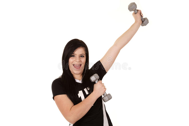 Girl having fun with weights. A teenage girl having some fun lifting weights stock image