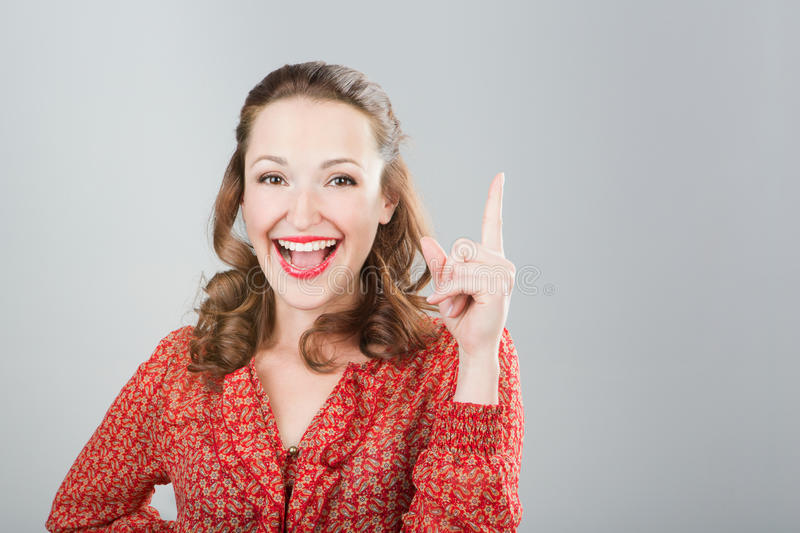 Girl having an idea. Smiling young woman with bright make-up with raised finger. Grey background. Studio shot stock photo