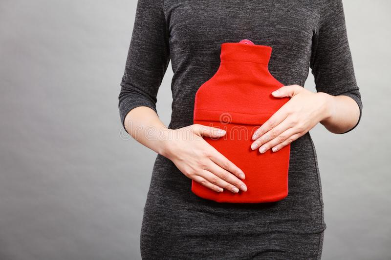 Girl having stomach ache, holding hot water bottle. Unrecognizable woman having strong stomach ache. Female suffer on belly pain, holding hot red water bottle on royalty free stock photo