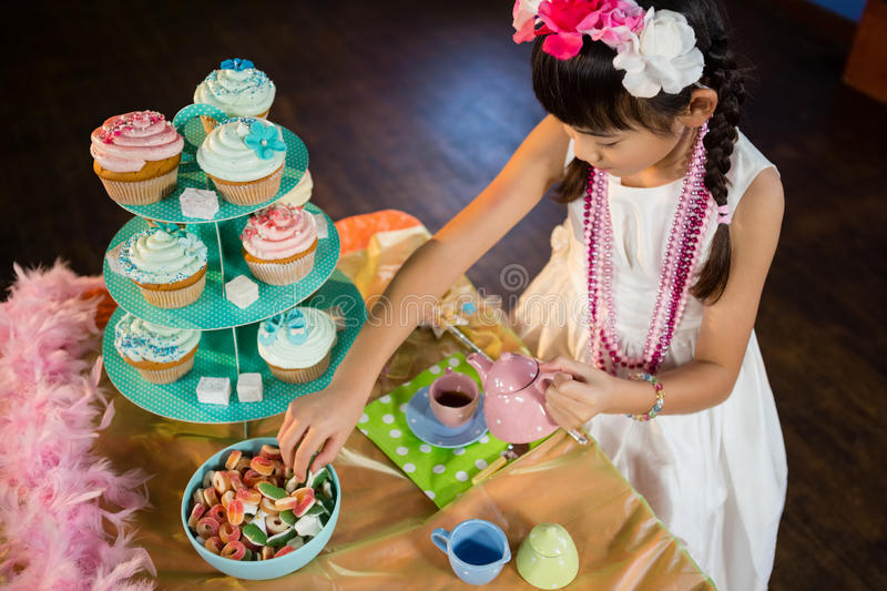Girl having tea and confectionery at table during birthday party royalty free stock image