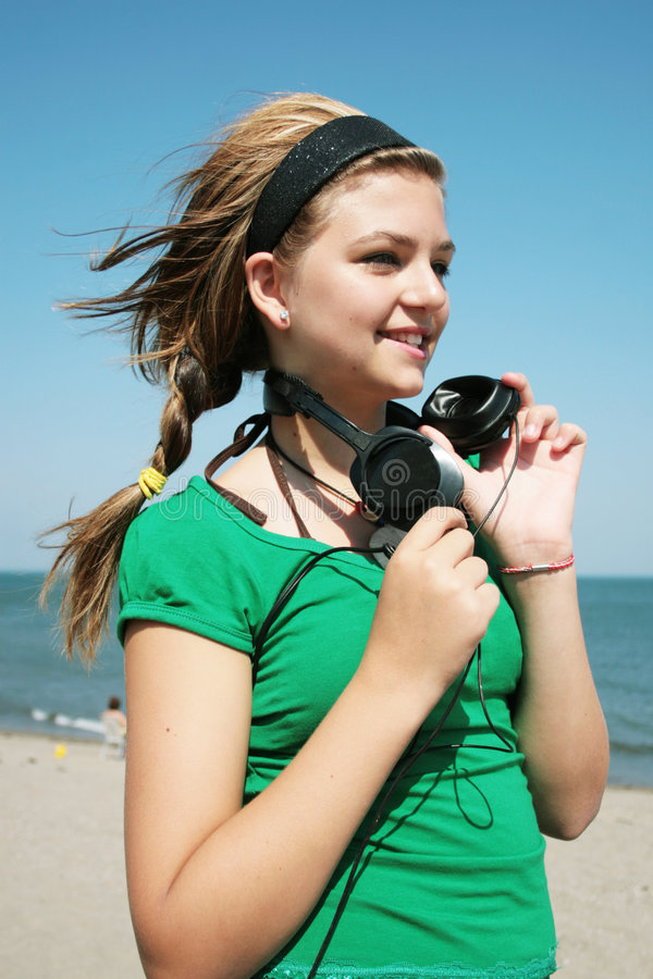 Girl with headphone. Pretty girl with headphone at the beach stock photography