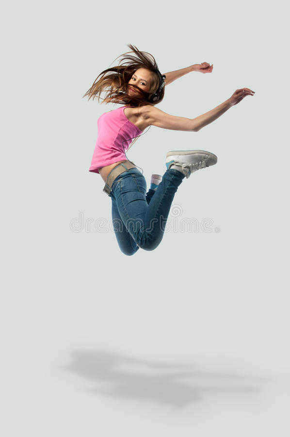 Girl in headphones jumps royalty free stock image