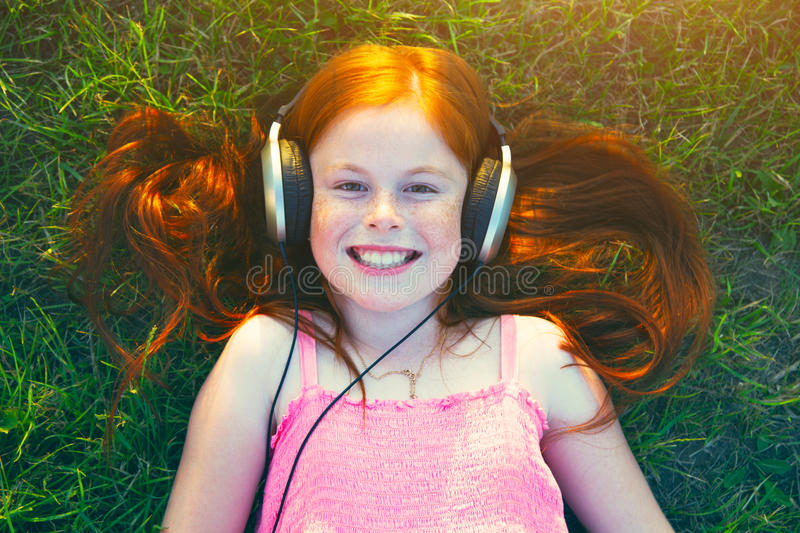 Girl with headphones listening to music. Redhead girl with headphones listening to music stock photo