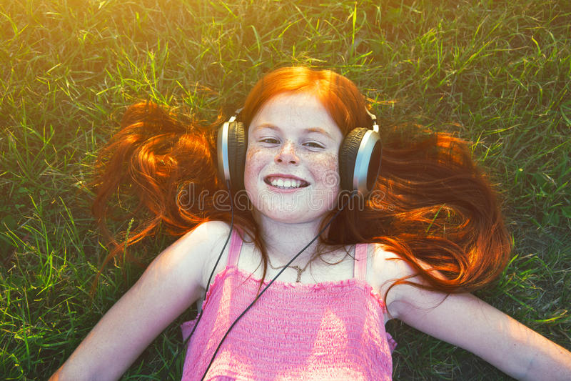Girl with headphones listening to music. Redhead girl with headphones listening to music royalty free stock image