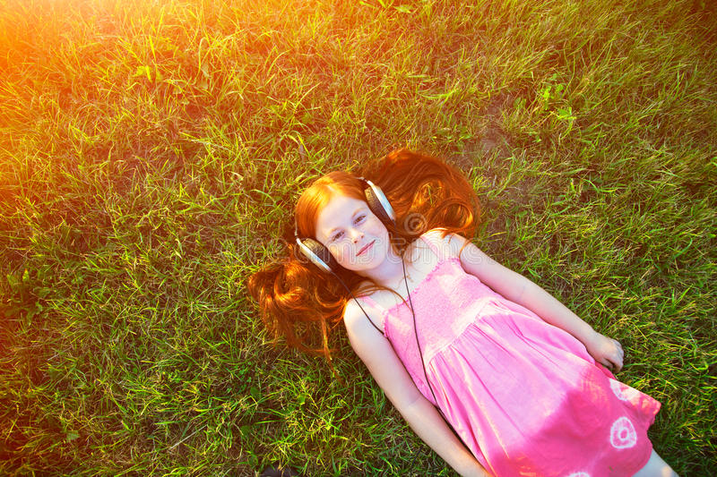 Girl with headphones listening to music. Redhead girl with headphones listening to music stock images