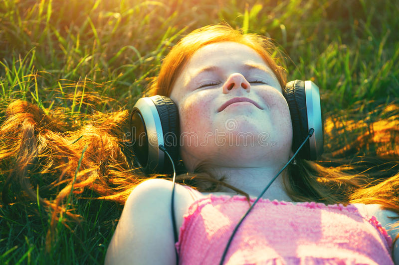 Girl with headphones listening to music. Redhead girl with headphones listening to music dreaming royalty free stock photography