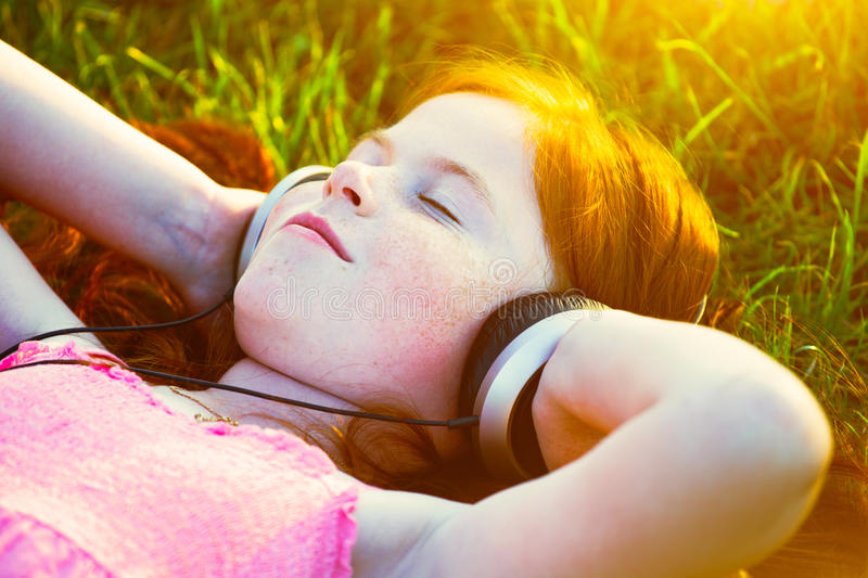 Girl with headphones listening to music. Redhead girl with headphones listening to music dreaming royalty free stock photo