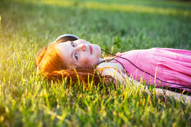 Girl with headphones listening to music. Redhead girl with headphones listening to music smiling royalty free stock image