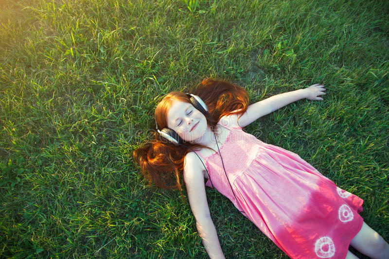 Girl with headphones listening to music. Redhead girl with headphones listening to music. view from above. space for text stock photography