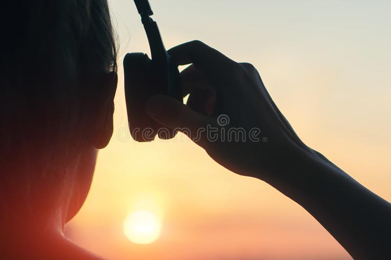 Girl in headphones listening to music in the city at sunset royalty free stock photos