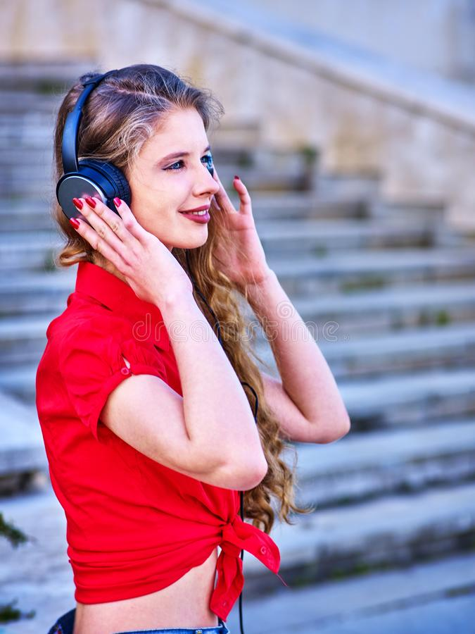 Girl in headphones listens to music walking down stairs stock photos