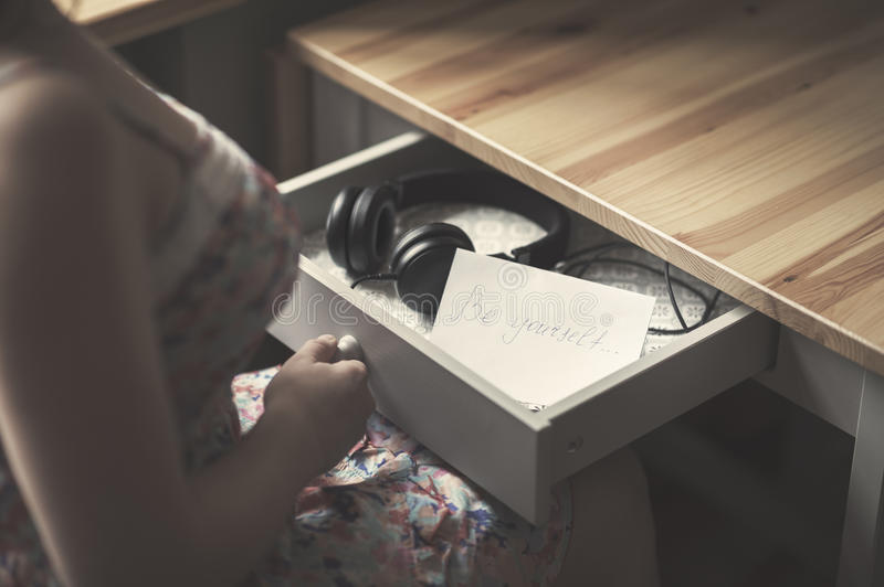The girl with headphones and message be yourself. The inscription on the paper be yourself. The concept of friendship and relationships royalty free stock images