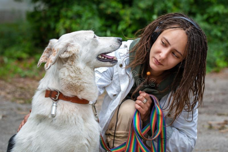 The girl in the headphones next to the dog pooch on the background of blurred green. Latino girl of appearance with dreadlocks royalty free stock photography
