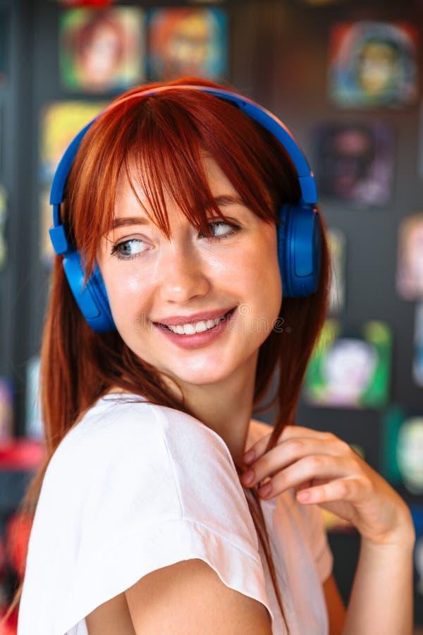 Girl with headphones in nightclub looking sideways royalty free stock images