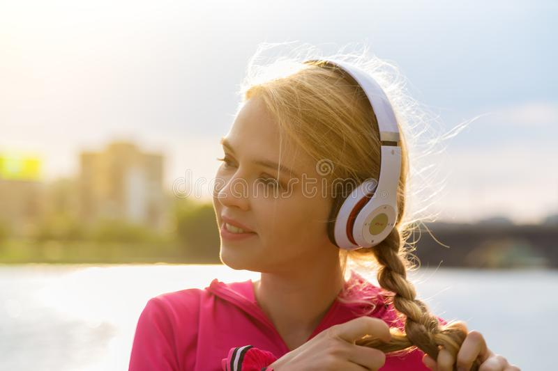 Girl in headphones and red shirt listens to mp3 music in city park. Teen portrait with hands to head backlight sun flare. Tone image. General cultural royalty free stock photography