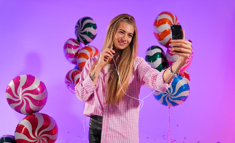 Girl in headphones with a smartphone, sings a song, on a purple background of candy, colored balloons royalty free stock image
