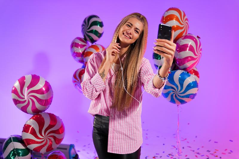 Girl in headphones with a smartphone, sings a song, on a purple background of candy, colored balloons stock images