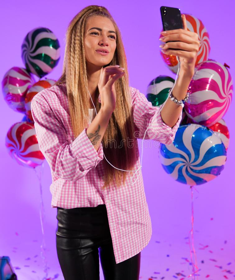 Girl in headphones with a smartphone, sings a song, on a purple background of candy, colored balloons royalty free stock photos