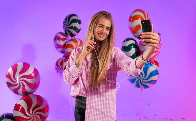 Girl in headphones with a smartphone, sings a song, on a purple background of candy, colored balloons royalty free stock images