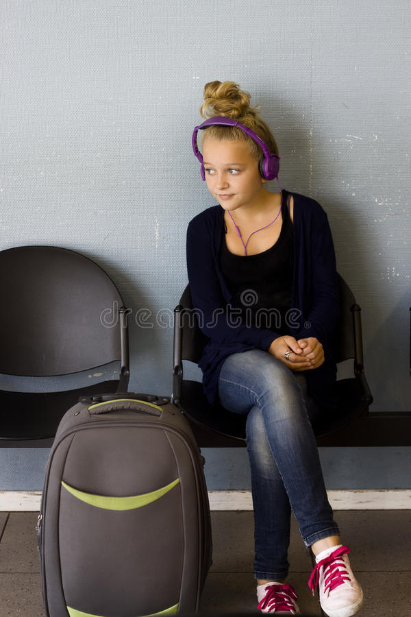 Girl with headphones waiting to travel stock image