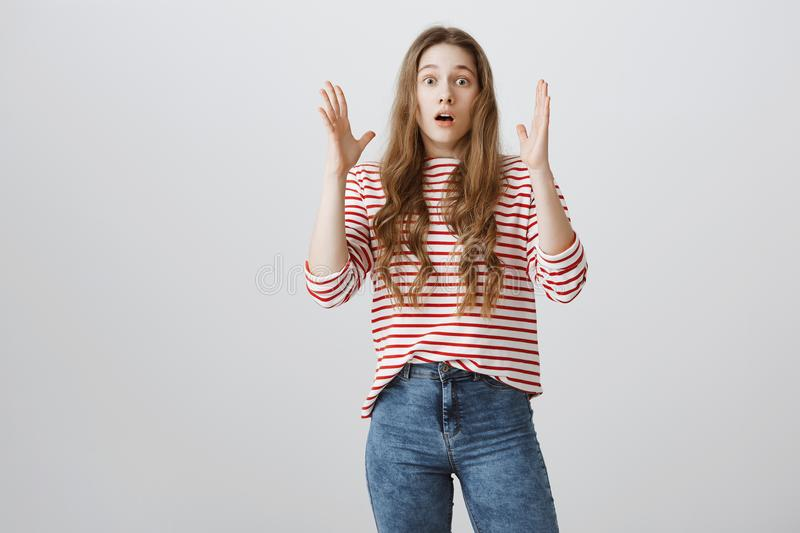 Girl heard unbelievable news. Studio shot of caucasian female student gasping, shaking hands near face and dropping jaw. Staring at camera with surprise and royalty free stock images