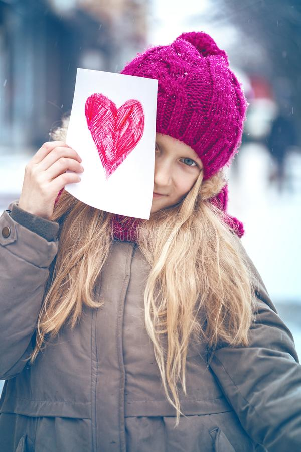 Girl with heart. Girl holding drawing with a heart on the valentines day royalty free stock image