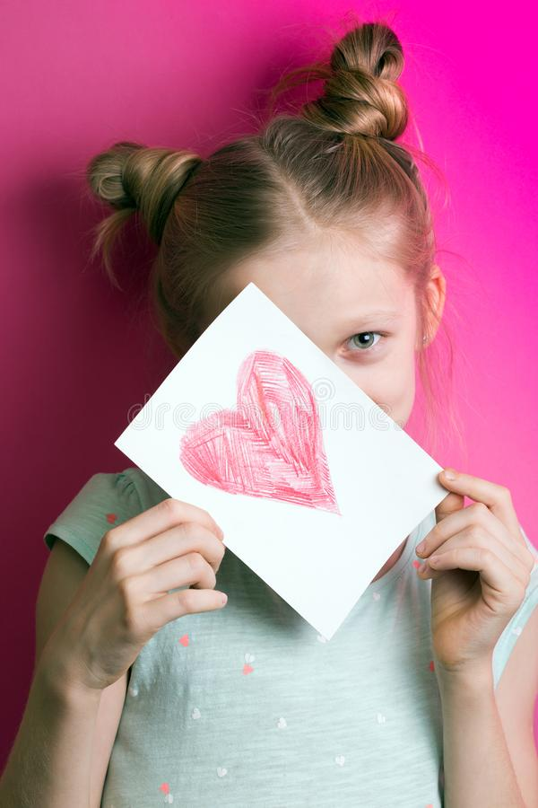 Girl with heart. Happy girl holding drawing with a heart on the valentines day royalty free stock images