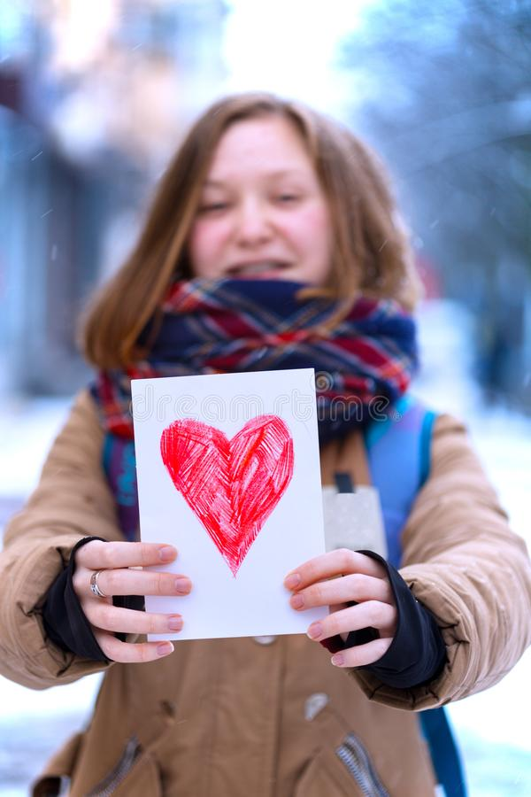 Girl with heart. Happy teen girl holding drawing with a heart on the valentines day stock image