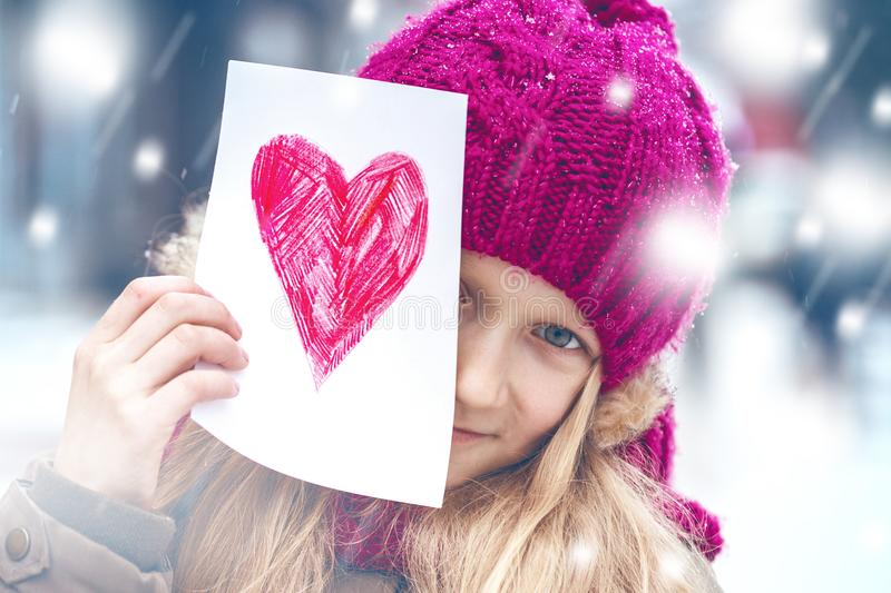 Girl with heart. Girl holding drawing with a heart on the valentines day royalty free stock images
