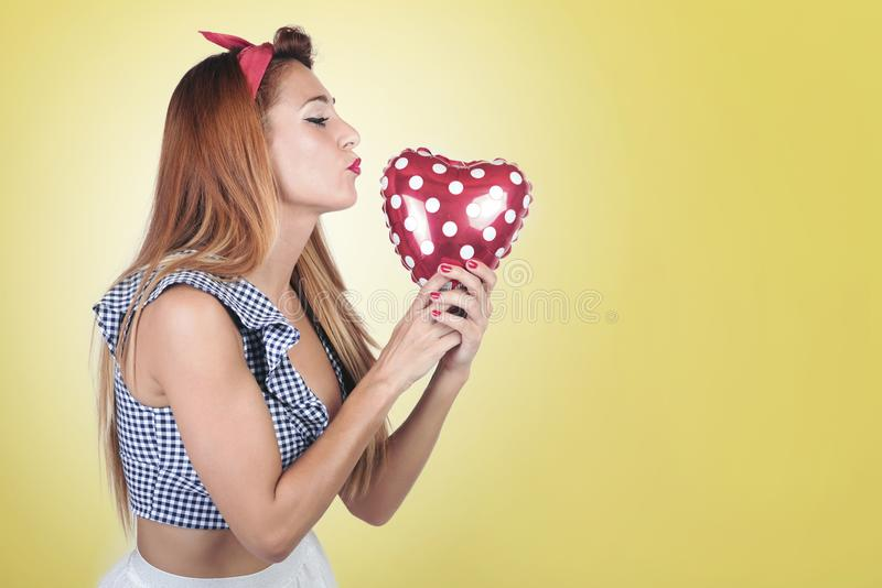 Girl with heart shape balloon. On yellow background royalty free stock photos