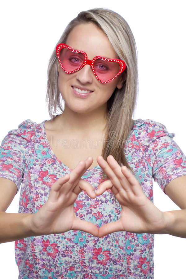 Girl with heart-shape sunglasses making heart sign. Pretty young woman with heart-shape sunglasses making heart sign on white stock photo